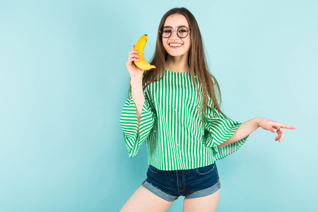 Portrait of attractive happy long-haired girl in striped shirt, glasses and jeans shorts holding banana like cellphone isolated on blue background with copyspace healthy way of life concept. Stock Photo