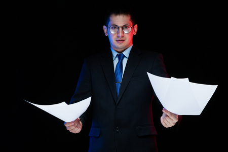 Young business man in black suit standing in office looking in camera with documents in his hands thoughtful handsome confident successful sophisticated classic smart elegant modern serious puzzled.