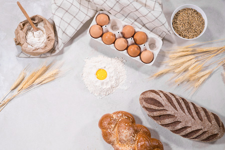 Top view of dough ingredients for cooking and loaves of bread on kitchen table isolated on grey backround home-bakery concept. Archivio Fotografico