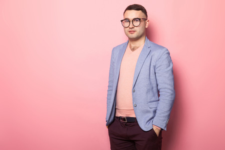Portrait of handsome man in eyeglasses, pink jumper and blue jacket holding hands in pockets isolated on pink background with copyspace male fashion advertising concept.