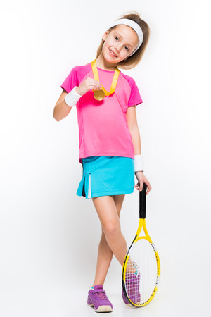 Adorable smiling little girl in sportswear holding tennis racket and medal in her hands on white background brunette caucasian beautiful attractive friendly lucky successful isolated gold silver bronze medal winner manage achieve.