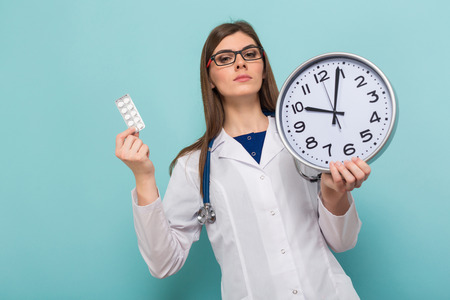 Portrait of serious female doctor in white coat and glasses with braces on teeth holds clock and pills isolated on blue background with copyspace time to take medicine concept.