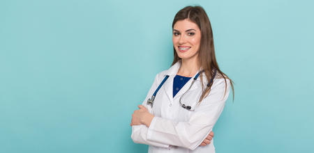 Portrait of female smiling brunette doctor with braces on her teeth in white coat with stethoscope and arms crossed isolated on blue background with copyspace head physician concept. Banco de Imagens