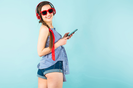 Portrait of brunette cheerful young woman DJ with in striped shirt and sunglasses on blue background listening to music in red headphones, using her smartphone and having fun.