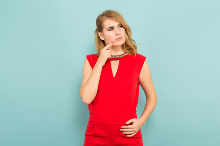 Portrait of thoughtful attractive blonde woman in red costume holding her finger on cheek isolated on blue background with copyspace sales discount difficult choice concept.