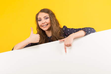 Portrait of attractive happy brunette woman in blouse isolated on yellow background pointing at emty blank board and holding her thumb up your text here concept. Stock Photo