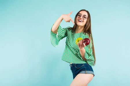 Portrait of attractive long-haired girl in striped shirt, glasses and jeans shorts hold red and green apples and show thumb up isolated on blue background with copyspace healthy way of life concept.