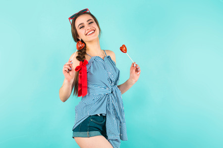Portrait of attractive young pin-up woman in striped shirt and jeans shorts with isolated on blue background with copyspace holding two heart-shaped candies on sticks.