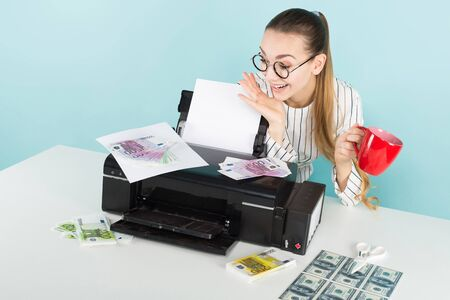 Portrait of attractive happy woman in striped shirt and eyeglasses isolated on blue background printing dollar and euro banknotes and holding red mug counterfeiter greed concept. Stock Photo