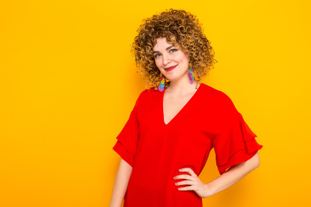 Portrait of a white woman with afrro curly hairstyle in red dress isolated on orange background with copyspace beauty salon advertisement concept.