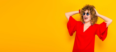 Portrait of a white woman with afrro curly hairstyle in red dress and sunglasses touching her head isolated on orange background with copyspace beauty salon advertisement concept horizontal picture.