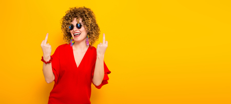 Portrait of a white woman with afrro curly hairstyle in red dress and sunglasses laughing and showing fuck sign isolated on orange background with copyspace beauty salon advertisement concept. Stock Photo