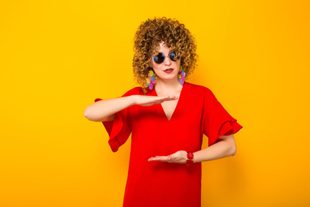 Portrait of a white woman with afrro curly hairstyle in red dress and sunglasses holding empty space isolated on orange background with copyspace beauty salon advertisement concept.
