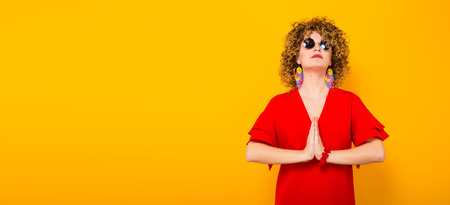 Portrait of a white woman with afrro curly hairstyle in red dress and sunglasses holding palms together like in pray isolated on orange background with copyspace beauty salon advertisement concept.