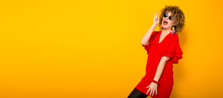 Portrait of a white woman with afrro curly hairstyle in red dress and sunglasses holding fingers crossed isolated on orange background with copyspace asking for good luck concept.