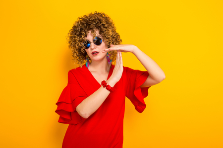 Portrait of a white woman with afrro curly hairstyle in red dress and sunglasses showing time out sign isolated on orange background with copyspace.