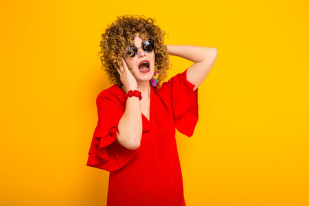 Portrait of a shocked white woman with afrro curly hairstyle in red dress and sunglasses touching her head isolated on orange background with copyspace beauty salon advertisement concept.