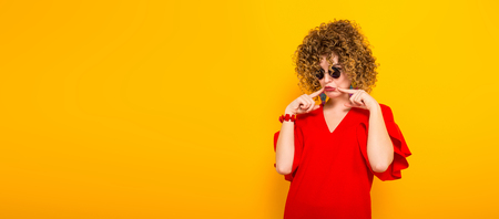Portrait of a white woman with afrro curly hairstyle in red dress and sunglasses making upset face isolated on orange background with copyspace horizontal picture.