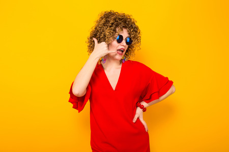 Portrait of a white woman with afrro curly hairstyle in red dress and sunglasses showing call me gesture isolated on orange background with copyspace.