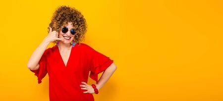 Portrait of a white woman with afrro curly hairstyle in red dress and sunglasses showing call me gesture isolated on orange background with copyspace horizontal picture. Stock Photo