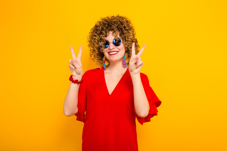 Portrait of a white woman with afrro curly hairstyle in red dress and sunglasses showing two fingers victory sign isolated on orange background with copyspace.