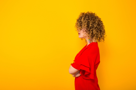 Portrait of a white woman with afrro curly hairstyle in red dress and sunglasses standing sideways with arms crossed isolated on orange background with copyspace beauty salon advertising concept.