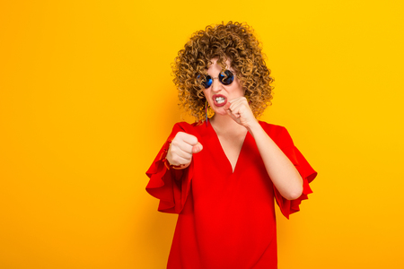Portrait of a white woman with afrro curly hairstyle in red dress and sunglasses holding fists in front of her ready to fight isolated on orange background with copyspace. Stock Photo