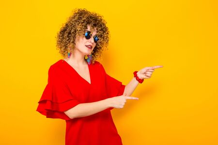 Portrait of a white woman with afrro curly hairstyle in red dress and sunglasses pointing at empty place with your text isolated on orange background with copyspace beauty salon advertisement concept. Stock Photo