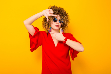 Portrait of a white woman with afrro curly hairstyle in red dress and sunglasses making a camera frame with fingers isolated on orange background with copyspace beauty salon advertising concept.