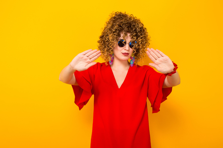 Portrait of a white woman with afrro curly hairstyle in red dress and sunglasses holding palms in front of her stop gesture isolated on orange background with copyspace.
