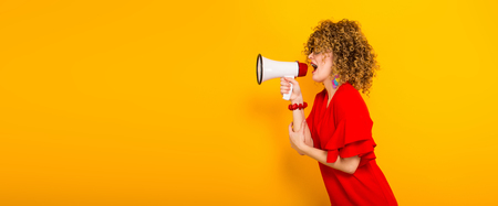 Portrait of a white woman with afrro curly hairstyle in red dress and sunglasses speaking into megaphone isolated on orange background with copyspace making announcement concept horizontal.