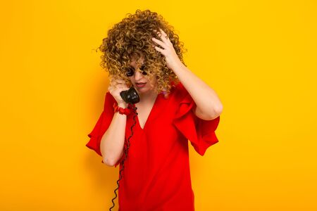 Portrait of a white woman with afrro curly hairstyle in red dress and sunglasses speaking on vintage phone isolated on orange background with copyspace.