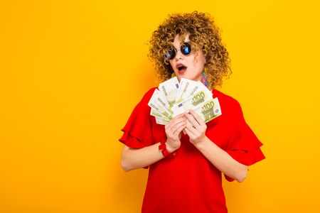 Portrait of a white surprised woman with afrro hairstyle in red dress and sunglasses holding fan of euro bills isolated on orange background with copyspace winning in lottery money withdraw concept.