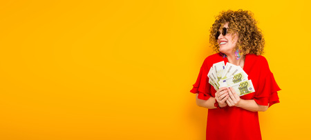 White happy woman with afrro hairstyle in red dress and sunglasses holding fan of euro bills isolated on orange background with copyspace winning in lottery money withdraw concept horizontal picture. Stock Photo