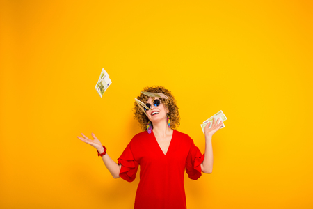 Portrait of a white happy woman with afrro hairstyle in red dress and sunglasses throwing euro bills isolated on orange background with copyspace winning in lottery money withdraw concept. Stock Photo