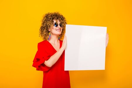 Portrait of a white woman with afrro curly hairstyle in red dress and sunglasses holding white blank board isolated on orange background your text here concept.