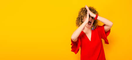 Portrait of a white woman with afrro curly hairstyle in red dress and sunglasses with hands up in front of her face isolated on orange background with copyspace.