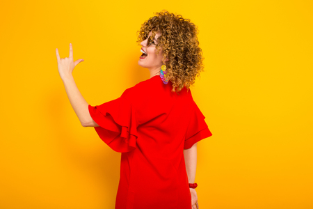 Portrait of a white woman with afrro curly hairstyle in red dress and sunglasses showing rock sign gesture isolated on orange background with copyspace beauty salon advertisement concept.