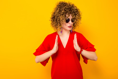 Portrait of a white cheerful woman with afrro curly hairstyle in red dress and sunglasses holding something in her hands isolated on orange background with copyspace advertising concept.