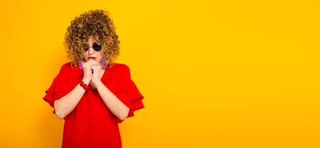 Portrait of a white cheerful woman with afrro curly hairstyle in red dress and sunglasses holding hands together hoping for the better isolated on orange background with copyspace horizontal picture.