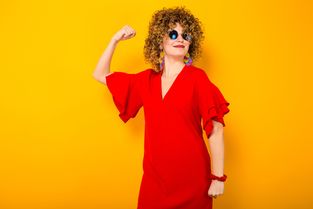 Portrait of a white woman with afrro curly hairstyle in red dress and sunglasses showing her muscles isolated on orange background with copyspace.