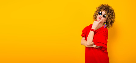 Portrait of a white woman with afrro curly hairstyle in red dress and sunglasses propping up her chin isolated on orange background with copyspace beuty salon advertising concept horizontal picture. Stock Photo