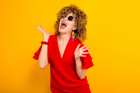 Portrait of a white woman with afrro curly hairstyle in red dress and sunglasses screaming with palms spread isolated on orange background with copyspace.