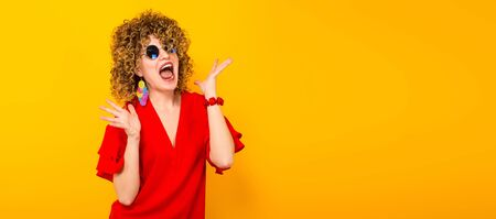 Portrait of a white woman with afrro curly hairstyle in red dress and sunglasses screaming with palms spread isolated on orange background with copyspace horizontal picture.