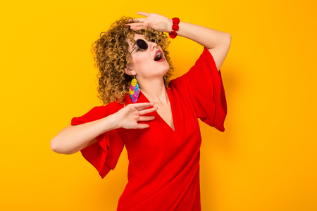 Portrait of a white woman with afrro curly hairstyle in red dress and sunglasses holds palm near forehead in shock isolated on orange background with copyspace.