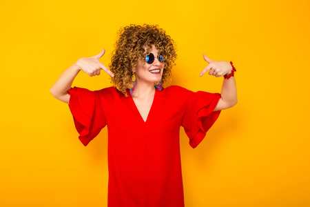 Portrait of a white woman with afrro curly hairstyle in red dress and sunglasses pointing with fingers at herself isolated on orange background with copyspace beauty salon advertisement concept.