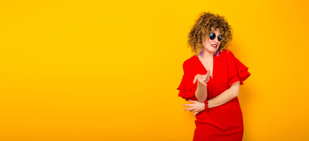 Portrait of a white woman with afrro curly hairstyle in red dress and sunglasses showing dobt isolated on orange background with copyspace horizontal picture. Stock Photo