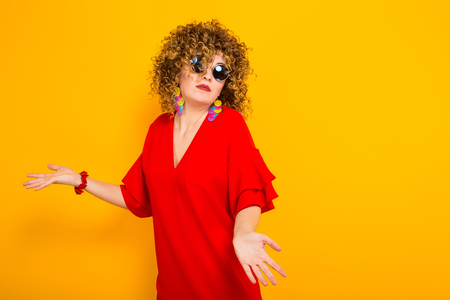 Portrait of a white woman with afrro curly hairstyle in red dress and sunglasses holds hands spread doesnt know what to do isolated on orange background with copyspace.