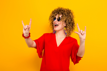 Portrait of a white woman with afrro curly hairstyle in red dress and sunglasses showing rock signs gesture isolated on orange background with copyspace advertising concept.