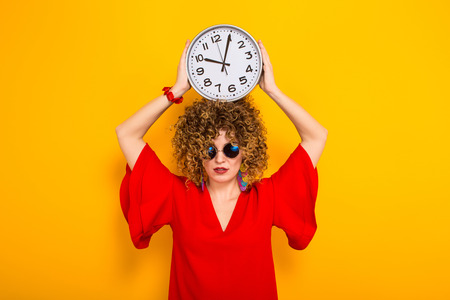 Portrait of a white woman with afrro curly hairstyle in red dress and sunglasses holding watches above her head isolated on orange background with copyspace punctuality being on time or late concept.
